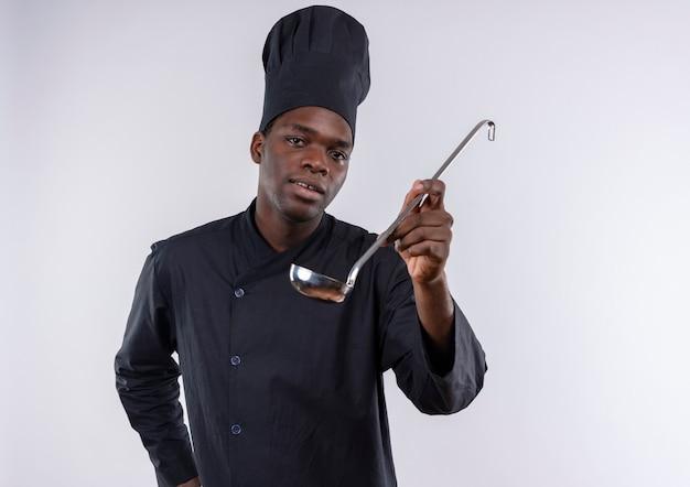 シェフの制服を着た若い喜んでいるアフリカ系アメリカ人の料理人は、コピースペースで白いおたまを保持します