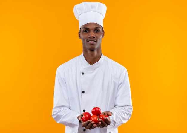 シェフの制服を着た若い喜んでいるアフリカ系アメリカ人の料理人は、オレンジ色の壁に分離された両手でジャガイモを保持します