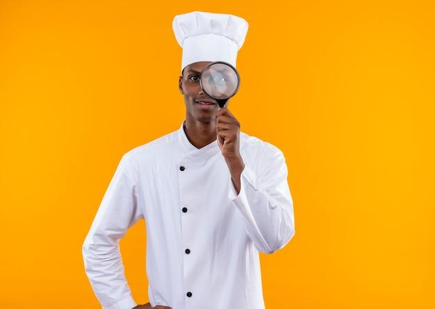 シェフの制服を着た若いアフリカ系アメリカ人の料理人は、オレンジ色の壁に隔離された虫眼鏡またはルーペを通して見えます