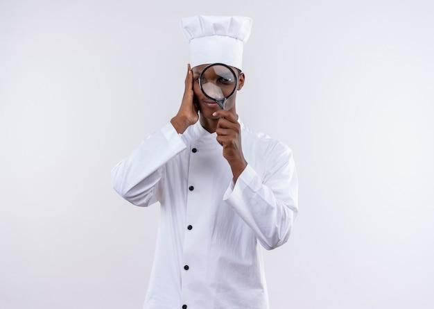 シェフの制服を着た若い喜んでいるアフリカ系アメリカ人の料理人は、白い壁に隔離された虫眼鏡またはルーペを通して見えます