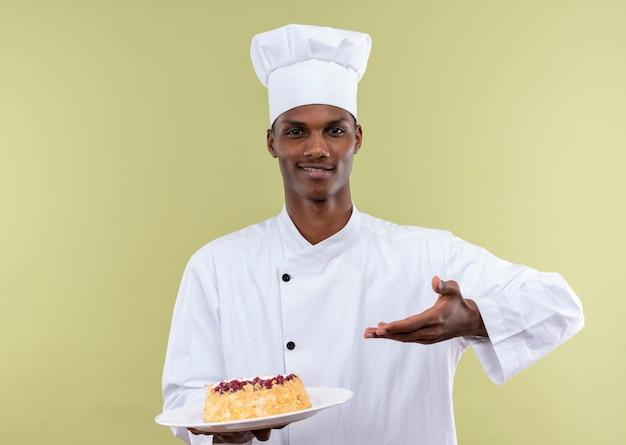 若い喜んでいるアフリカ系アメリカ人の料理人は、白い皿の上のケーキと緑の壁に隔離された手でポイントでシェフの制服のポイントで