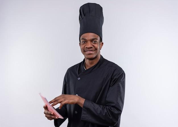 白い壁に隔離されたノートブックでシェフの制服のポイントで若い喜んでアフリカ系アメリカ人の料理人