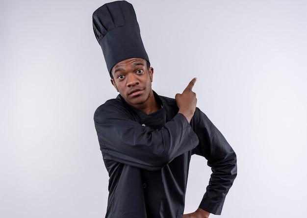 若い喜んでいるアフリカ系アメリカ人の料理人が白い壁に隔離されたシェフの制服のポイントで