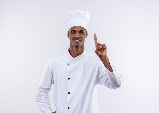 シェフの制服を着た若いアフリカ系アメリカ人の料理人は、白い壁に隔離されたポイントを上に向けます