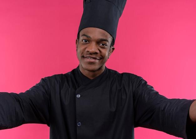 シェフの制服を着た若いアフリカ系アメリカ人の料理人は、ピンクの壁に隔離された抱擁を装います