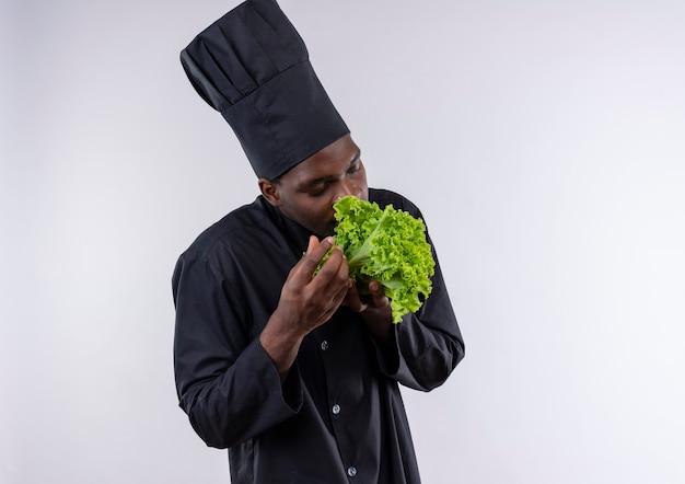 シェフの制服を着た若いアフリカ系アメリカ人の料理人は、コピースペースで白のサラダの匂いを嗅ぐふりをします 無料写真