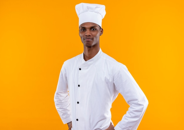 シェフの制服を着た若い喜んでアフリカ系アメリカ人の料理人は、オレンジ色の壁に隔離された腰に手を置きます