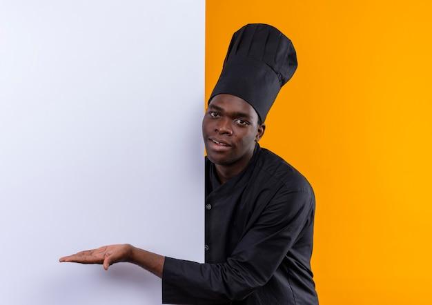 シェフの制服を着た若い喜んでいるアフリカ系アメリカ人の料理人が後ろに立って、コピースペースのあるオレンジ色の白い壁を手で指しています