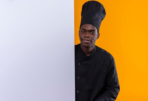 コピースペースとオレンジ色のスペースに分離された白い壁の後ろに立っているシェフの制服を着た若い喜んでアフリカ系アメリカ人の料理人