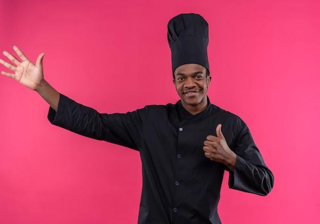 シェフの制服を着た若いアフリカ系アメリカ人の料理人が親指を立てて、ピンクの壁に手を離して横を指しています