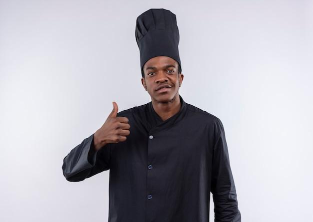 白い壁に隔離されたシェフの制服の親指で若い喜んでアフリカ系アメリカ人の料理人