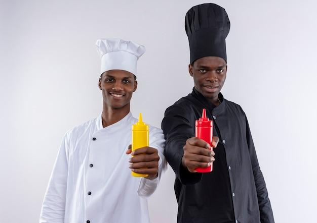 シェフの制服を着た若いアフリカ系アメリカ人の料理人は、白い壁に分離されたマスタードとケチャップを保持します