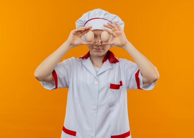Young pleased blonde female chef in chef uniform closes eyes with eggs isolated on orange wall