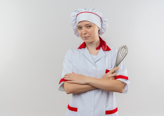 Young pleased blonde female chef in chef uniform crosses arms and holds whisk isolated on white wall