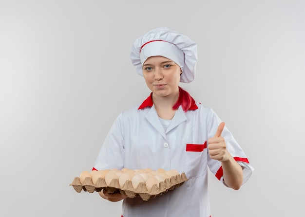 Young pleased blonde female chef in chef uniform holds batch of eggs and thumbs up isolated on white wall