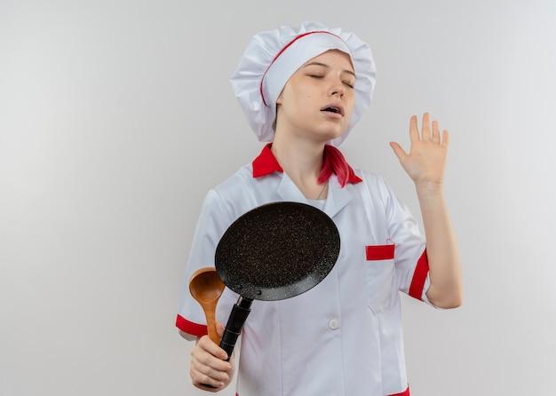 Il giovane chef femminile biondo felice in uniforme del cuoco unico tiene la padella e alza la mano con gli occhi chiusi isolati sulla parete bianca