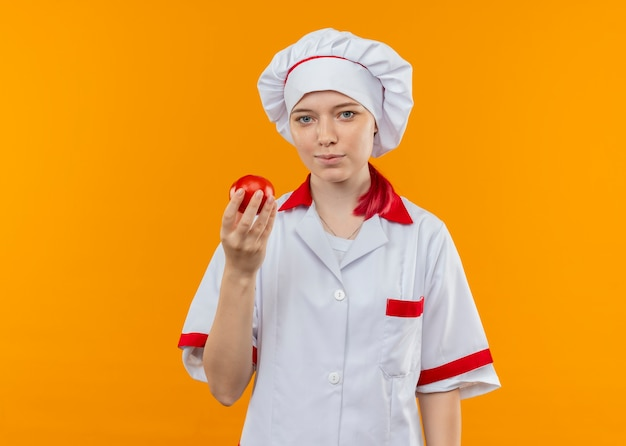 Young pleased blonde female chef in chef uniform holds tomato and looks isolated on orange wall