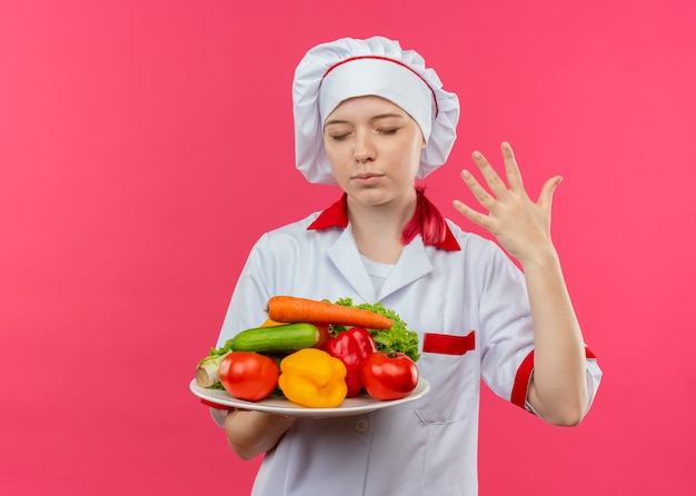 Young pleased blonde female chef in chef uniform holds vegetables on plate and raises hand isolated on pink wall