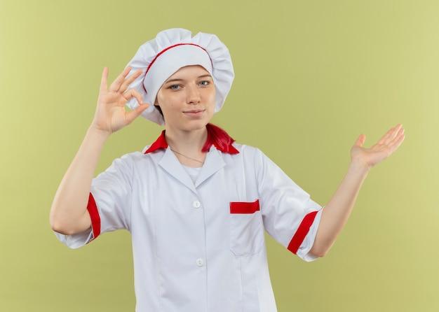 シェフの制服のジェスチャーで若い喜んでいる金髪の女性シェフは、緑の壁に隔離された側の手話とポイントをok