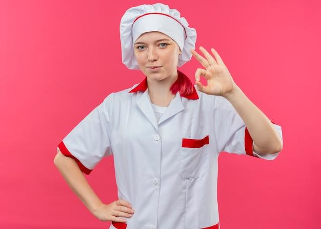 ピンクの壁に分離されたシェフの制服のジェスチャーでokハンドサインで若い喜んで金髪の女性シェフ