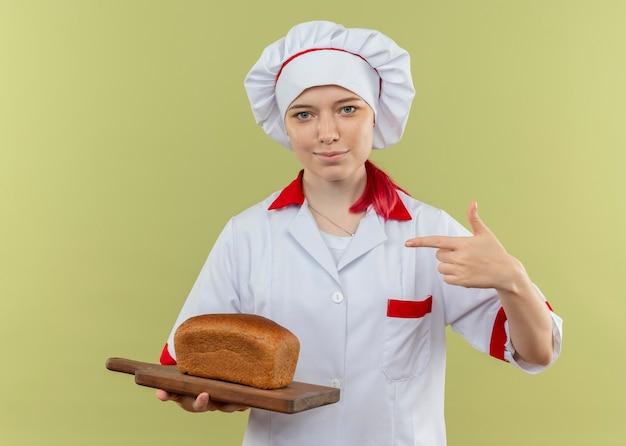 シェフの制服を着た若い喜んで金髪の女性シェフは、緑の壁に分離されたまな板の上のパンを保持し、ポイントします