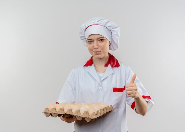 Молодая довольная блондинка-шеф-повар в форме шеф-повара держит партию яиц и показывает палец вверх, изолированную на белой стене