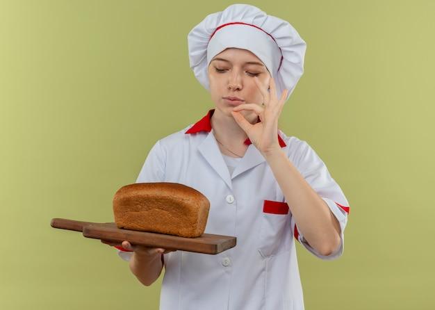 シェフの制服を着た若い喜んで金髪の女性シェフはまな板にパンを保持し、緑の壁に分離されたおいしいサインをジェスチャー