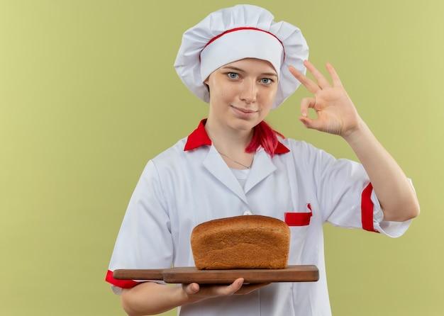 シェフの制服を着た若い喜んで金髪の女性シェフはまな板にパンを保持し、緑の壁に分離された手振りok