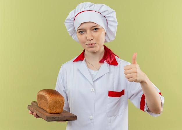シェフの制服を着た若い喜んで金髪の女性シェフはまな板にパンを保持し、緑の壁に分離された親指を立てる