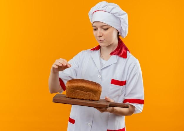 シェフの制服を着た若い喜んで金髪の女性シェフは、オレンジ色の壁で隔離まな板にパンを保持します。