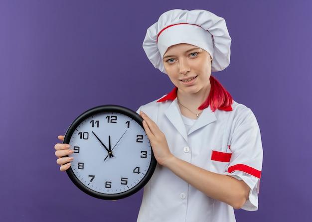 シェフの制服を着た若い喜んで金髪の女性シェフは時計を保持し、紫色の壁に孤立して見える