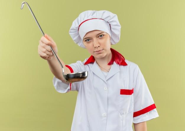 Молодая довольная блондинка-шеф-повар в форме шеф-повара держит черпак на зеленой стене