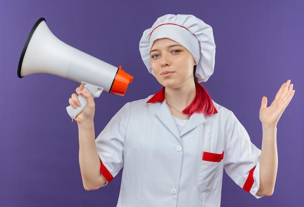 シェフの制服を着た若い喜んで金髪の女性シェフは、スピーカーを保持し、紫色の壁に隔離された手を上げます