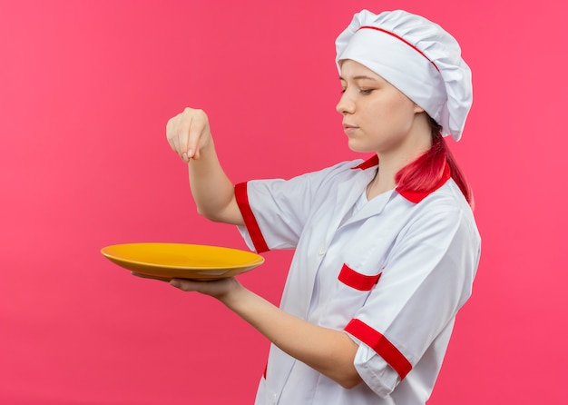 シェフの制服を着た若い喜んで金髪の女性シェフは、プレートを保持し、ピンクの壁に分離された塩のふりをします