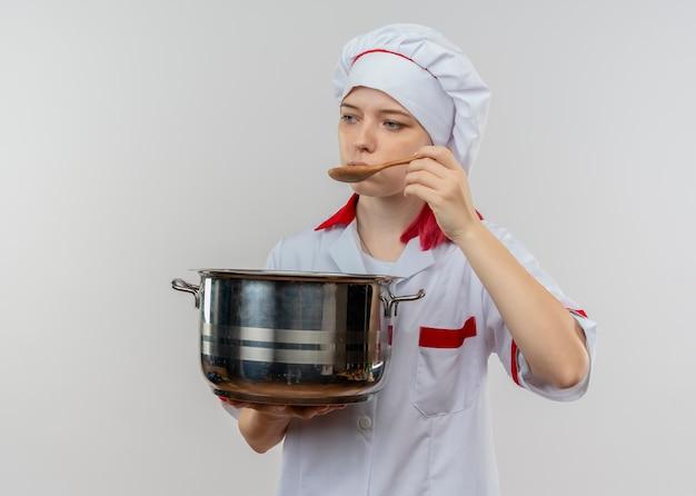 シェフの制服を着た若い喜んで金髪の女性シェフが鍋を保持し、白い壁に隔離されたスプーンで試してみるふりをします