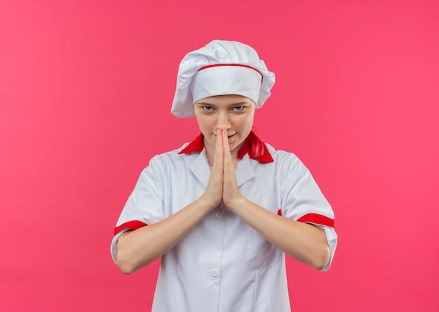 Молодая довольная блондинка женщина-повар в форме шеф-повара сжимает руки вместе, изолированные на розовой стене