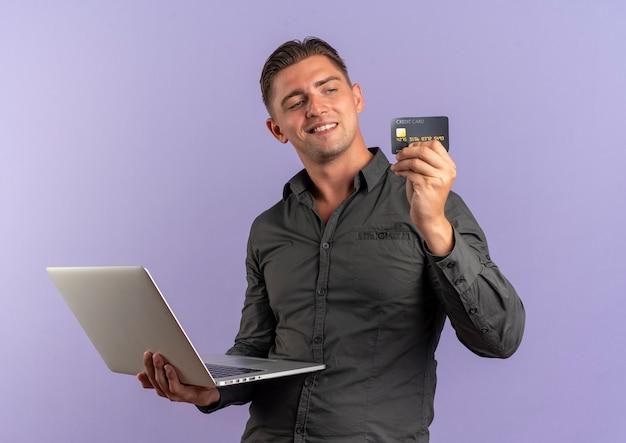 Giovane uomo bello biondo contento tiene il computer portatile e guarda la carta di credito