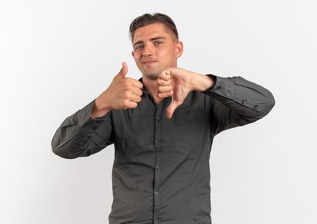 I giovani felici uomo bello biondo thumbs up e thumbs down isolati su sfondo bianco con spazio di copia