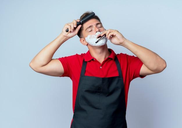 Молодой довольный светловолосый парикмахер в униформе измазал лицо пеной для бритья, держа в руке опасную бритву, расчесывая волосы, изолированные на белом пространстве с копией пространства