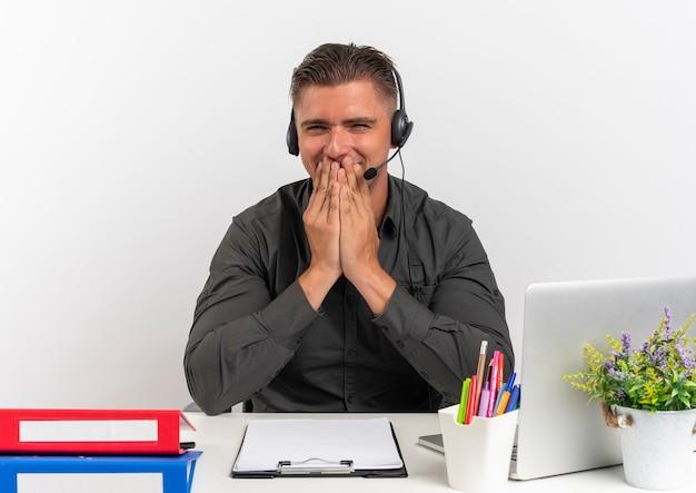 L'uomo di lavoratore di ufficio bionda felice giovane sulle cuffie si siede alla scrivania con strumenti di ufficio utilizzando il computer portatile mette le mani sulla bocca