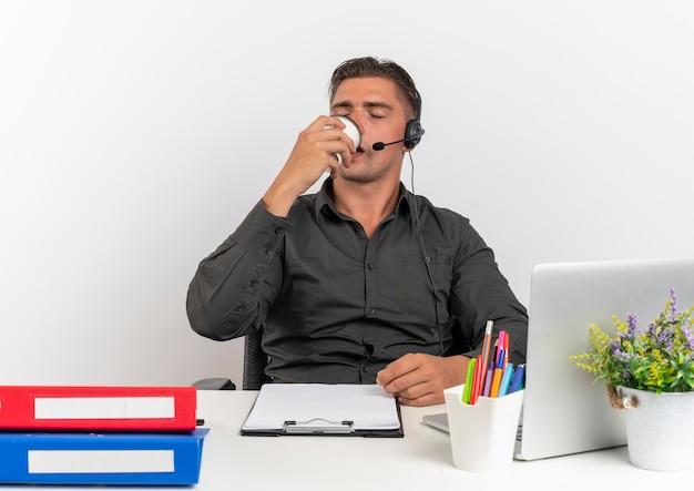 Молодой довольный белокурый человек офисного работника в наушниках сидит за столом с офисными инструментами, используя ноутбук, пьет чашку кофе на белом фоне с копией пространства