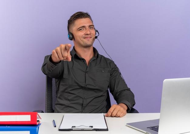 헤드폰에 젊은 기쁘게 금발 회사원 남자 복사 공간이 보라색 배경에 고립 된 카메라에서 노트북 포인트를 사용하여 사무실 도구와 책상에 앉아
