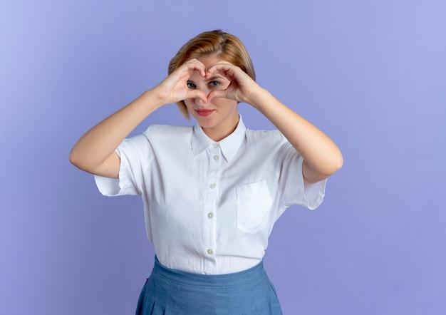 Giovane ragazza russa bionda felice gesti e guarda attraverso il segno della mano del cuore isolato su priorità bassa viola con lo spazio della copia