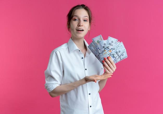 若い喜んでいる金髪のロシアの女の子は、コピースペースでピンクのお金を保持し、ポイントします