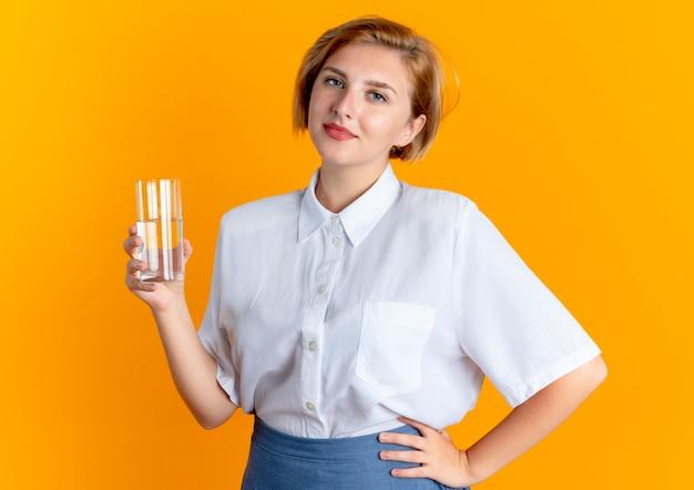 La giovane ragazza russa bionda felice tiene il bicchiere d'acqua isolato su sfondo arancione con spazio di copia