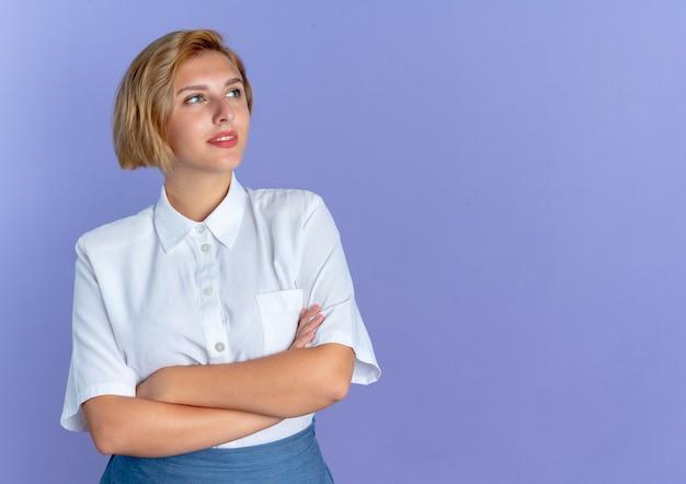 Молодая довольная русская блондинка смотрит в сторону со скрещенными руками, изолированными на фиолетовом фоне с копией пространства
