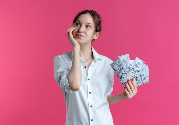 Young pleased blonde russian girl puts hand on face looks at side holding money on pink  with copy space