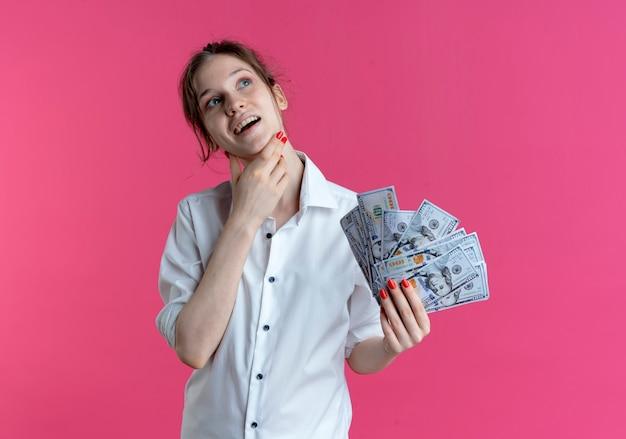 Молодая довольная русская блондинка кладет руку на подбородок, смотрит вверх, держа деньги на розовом с копией пространства