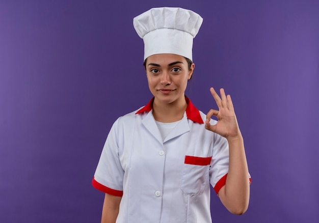 Young pleased caucasian cook girl in chef uniform gestures ok hand sign isolated on violet wall with copy space