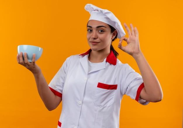 La giovane ragazza caucasica felice del cuoco in uniforme del cuoco unico tiene il segno giusto della mano di gesti e della ciotola isolato sulla parete arancio con lo spazio della copia